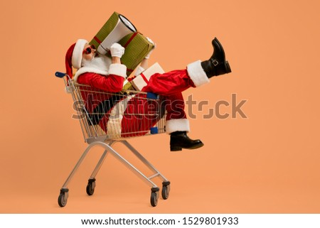 Authentic Santa Claus in red costume, white gloves and sunglasses shouting in white megaphone while sitting in shopping cart with present boxes. Senior man with real beard announcing about holidays