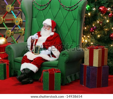 authentic santa claus sitting in large green chair surrounded by presents and decorations