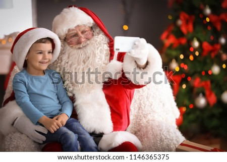 Authentic Santa Claus taking selfie with little boy indoors