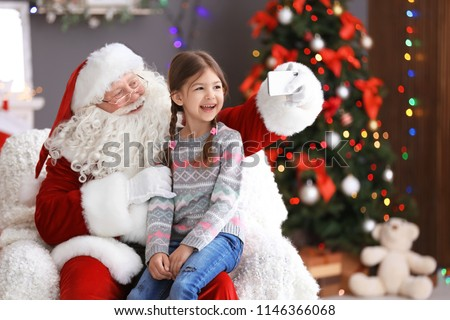 Authentic Santa Claus taking selfie with little girl indoors