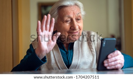 Authentic shot of a happy grandmother is making a selfie or video call to relatives with a smartphone at home. Concept of technology, modern generation,family, connection, authenticity