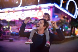 Authentic shot of a happy smiling father carrying his little daughter on a shoulders having fun together in amusement park with luna park lights at night.