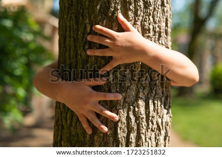 Authentic shot of a little girl is hugging a tree trunk on a sunny day.  Foto stock ©