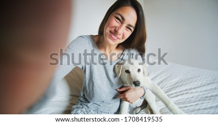 Authentic shot of an young happy woman is making a selfie or video call to a boyfriend with her puppy of Labrador Retriever dog in a bed. Concept of technology, connection,pets, family authenticity