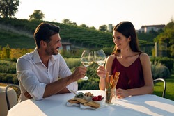 Authentic shot of happy couple in love is enjoying romantic dinner together and cheering with white wine glasses to celebrate their anniversary and timeless love on scenic vineyards background.