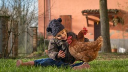 Authentic shot of happy little smiling girl is playing with hen outside the countryside house in a sunny autumn day. Concept: love for animals and nature, agriculture, authenticity