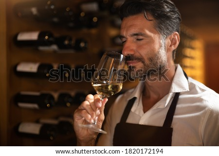 Authentic shot of successful male sommelier is tasting a flavor and checking white wine quality poured in transparent glass in a wine cellar. Foto stock ©