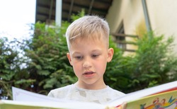 Authentic Smart beautiful boy learning to read book. Handsome genious child reading outdoors on a sunny day.