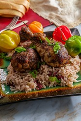 Authentic spicy Jamaican jerk chicken legs with scotch bonnet chili peppers served with coconut rice and peas