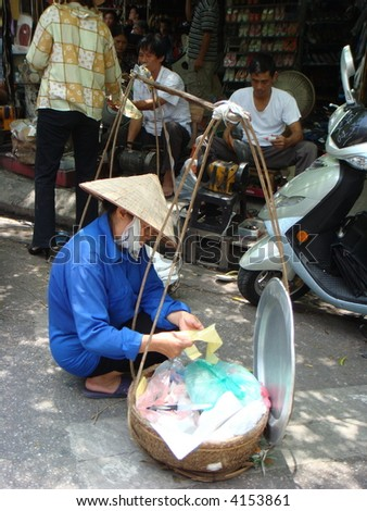Authentic Vietnam street View: Vietnamese street vendor with bamboo hat