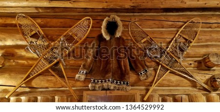 Authentic, Vintage Alaskan Snow Shoe Pairs Hung on a Log Cabin Wall with a Hooded Animal Fur Coat in the Center of It; Design Ideas, Winter Accessories, Cozy, Log Cabin Decor