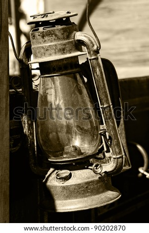 Authentic vintage lantern from American old west era attached to an old wagon (sepia tint added).