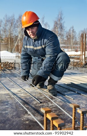 Authentic worker builder positioning and assembling reinforcement rods elements for concrete pouring at construction building area site