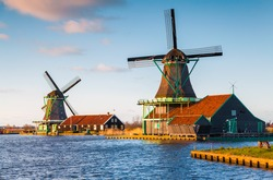 Authentic Zaandam mills on the water channel in Zaanstad village. Zaanse Schans Windmills and famous Netherlands canals, Europe.