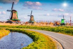 Authentic Zaandam mills on the water channel in Zaanstad village. Zaanse Schans Windmills and famous Netherlands canals, Europe
