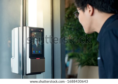 Authentication by facial recognition concept. Biometric admittance control device for security system. Asian man using face scanner to unlock glass door in office building.