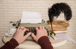 Author's woman hands typing something on an old mechanical typewriter