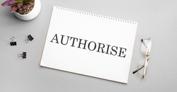 AUTHORISE is written in a white notebook next to a pencil, black-framed glasses and a green plant.