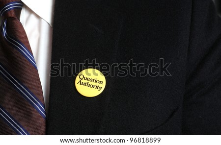 Authority Questions Authority/Close up of uncopyrighted Question Authority button pinned to black camels hair Brooks Brothers suit jacket with tie & white shirt visible.