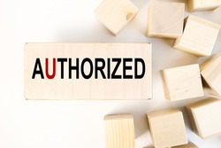 AUTHORIZED, TEXT on a wood block on a light background