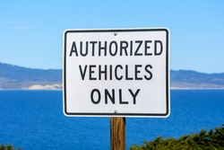Authorized Vehicles Only road sign. Calm water of the bay and coastline is visible in the distance.