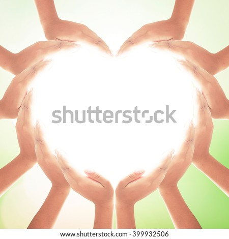 Autism awareness and help concept: People hands in shape of heart on blurred beautiful natural background.