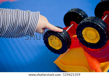Autistic behavior? Toddler's hand turning wheels on plastic toy.