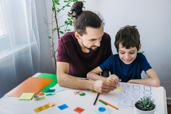 Autistic boy during therapy at home with his father with learning and having fun together. Autism awareness concept