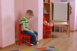 autistic boy. The child sits in the corner. Punished child. Frustrated, thoughtful boy