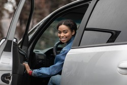 Auto blogger and test drive cars, good auto offer and ad. Smiling young african american lady driver sitting in car behind steering wheel, opens door and looks back at road in city, empty spaces