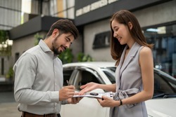 Auto business, car sale, consumerism and people concept - woman Sign Contract with car dealer in auto show. car salesman is making deal with lender. Used cars cheaper than new cars. But to buy a used