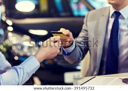 auto business, sale and people concept - close up of customer giving credit card to car dealer in auto show or salon #391495732