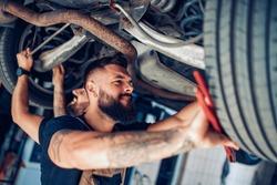 Auto car repair service center.Mechanics checking wheel bearings in car workshop.