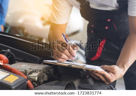 Auto check up and car service shop concept. Mechanic writing job checklist to clipboard to estimate repair quotation to client at workshop garage. Photo stock ©