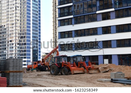 Auto crane and tractors at a construction site near a new residential building. Housing Renovation Program