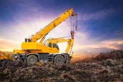 Auto crane on the ground at construction site with sunset background