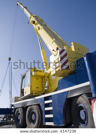 Auto-crane unloading against a blue sky