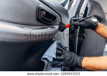 Auto detailing, worker cleans door trim with brush