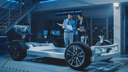 Auto Industry Design Facility: Male Chief Engineer Shows Car Blueprints Female Software Design and Integration Engineer. Electric Vehicle Platform Chassis Concept Has Wheels, Engine and Battery