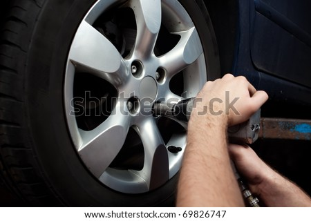 Auto mechanic changing wheel on car with pneumatic wrench