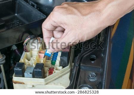Auto mechanic checking a car fuse