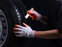 Auto mechanic checking a car tire on a black background,wood ruler measure the tread