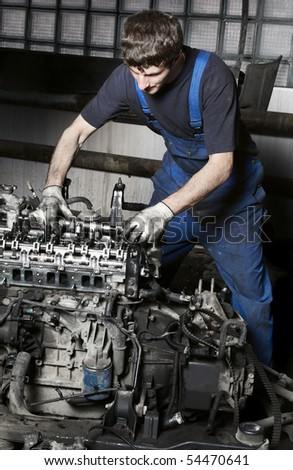 Auto mechanic checking an internal combustion engine.