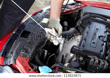 Auto mechanic checking oil. Car repair service.