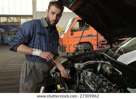 auto mechanic checking oil engine
