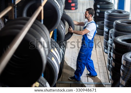 Auto mechanic  choose tire for car at a tire store #330948671