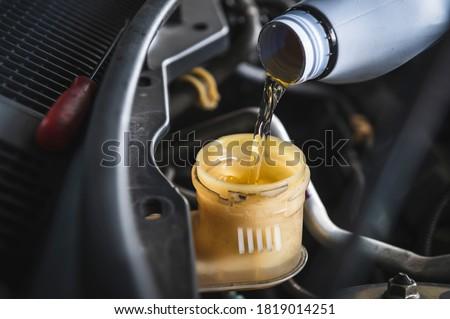 Auto mechanic filling DOT 4 brake fluid in brake fluid reservoir.