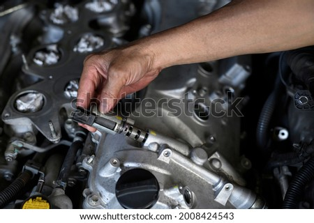 Auto mechanic hand installing variable valve timing solenoid on the engine. Photo stock ©