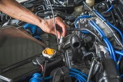 Auto mechanic hands installing a new iridium spark plugs.
