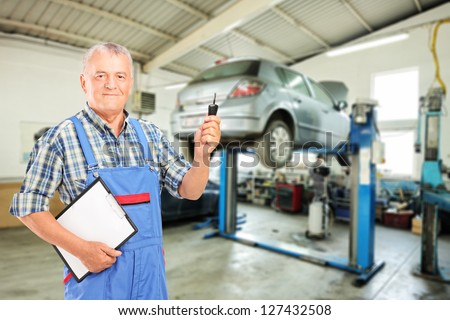 Auto mechanic holding a car key at auto repair shop during an automobile maintenance service